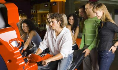 Group of friends at amusement arcade with two friends on motorbike game