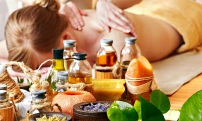 Woman receiving back massage with massage products in front of her