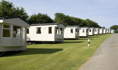 Multiple white caravans on grass on a sunny day with blue sky