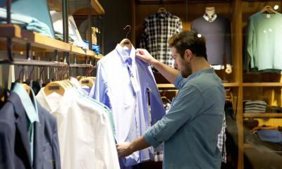 Man picking out blue shirt in clothes shop with other clothes in background
