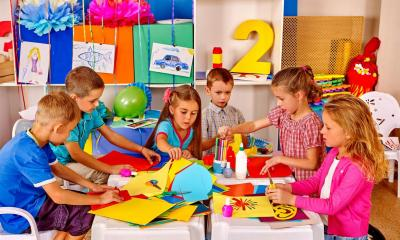 Multiple children at nursery drawing on coloured paper