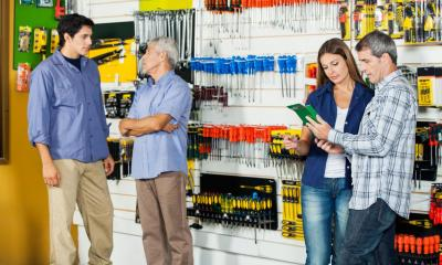 Two customers in DIY shop being served by employees with multiple tools in background