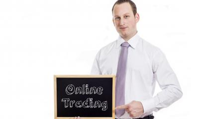 Man in white shirt pointing to text written on blackboard