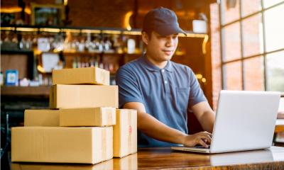 A small business owner checks his online orders and dispatches goods