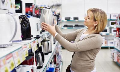 Woman holding kettle next to shelf of kettles in electrical shop