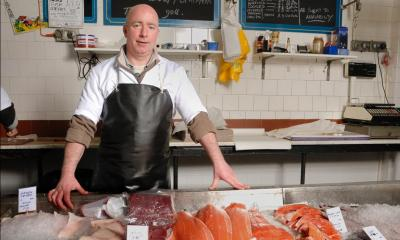Fishmonger in black apron stood behind table with various fish types on it