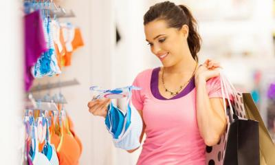 Woman in pink top holding lingerie in lingerie shop