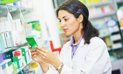 Pharmacist holding green medicine packet in pharmacy shop