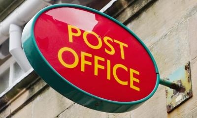 Red post office sign sticking out of beige wall