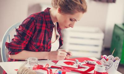 Woman in red shirt sat down at table making rural crafts