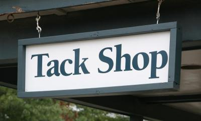 Green tack shop sign hanging down from wooden pillar