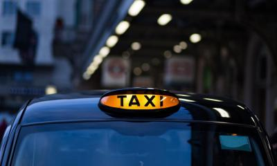 Black taxi with 'TAXI' sign lit up during night-time