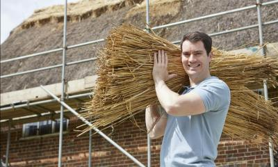 Man holding thatching materials with thatched house in background
