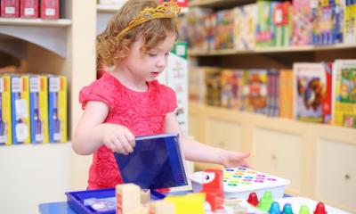 Little girl in pink top playing with different toys in toy shop