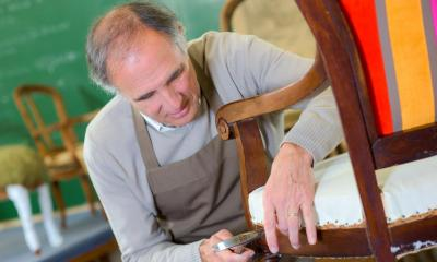 Man in grey jumper and brown dungarees repairing wooden chair