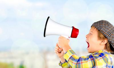 Little boy in a hat and shirt shouting into a white megaphone to gain publicity