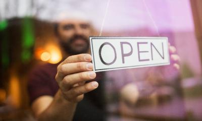 A small business owner turns the sign in the window as he opens his shop for the day