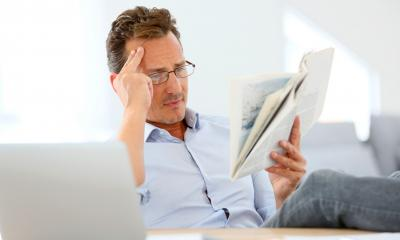 Business owner in glasses reading book about PR