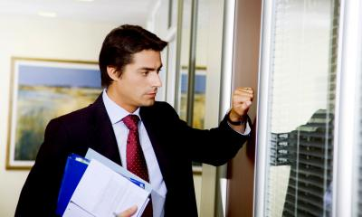 Man in a suit about to knock on a door to have a difficult conversation with an empployee