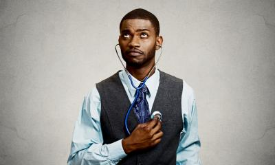 Male employee dressed smartly self-assessing himself with a stehoscope
