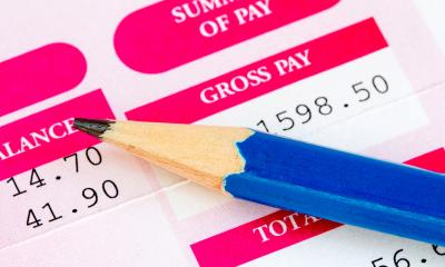 Pink payslip showing a persons wages with a blue pencil resting on top