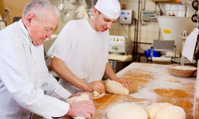 An apprentice wearing chef white kneading dough with his employer