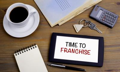 'TIME TO FRANCHISE' written on a tablet with various items surrounding it