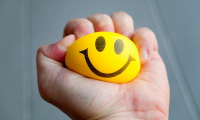 Person squeezing a yellow stress ball with a smiling face on it