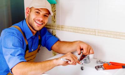 A plumber leant over a sink fixing a tap with tools