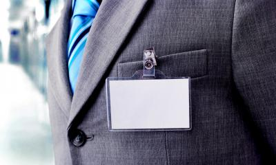 Close up of a business man wearing a suit with a blank name badge clipped to the pocket