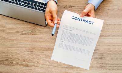 Overhead shot of an employer handing over a pen and an employment contract