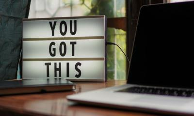 """YOU GOT THIS"" motivational florescent board next to laptop"