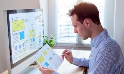 A website designer reads a client specification document and sketches - wireframe layout design for responsive web content