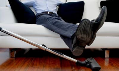 a businessman lifts his feet so that the floor can be vacuumed