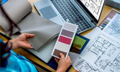 An interior designer is working with architect's drawings, material and colour samples representing self-employment concept