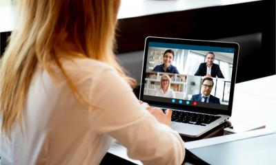 Rear view of businesswoman engaged in a virtual meeting on her laptop from home with diverse colleagues