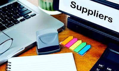 Desk with laptop, stationery and file labelled suppliers