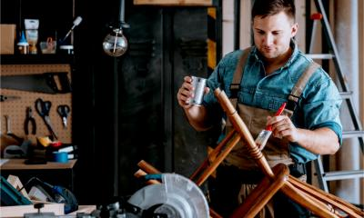 A self-employed carpenter repairs a chair
