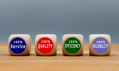 Row of dice with the words Service Quality Reliability and Efficiency on them