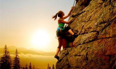 A woman is rock climbing - adventure and extreme sport concept