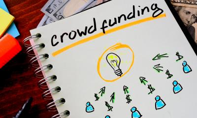 Notepad with 'crowd funding' written on the front cover with drawings below