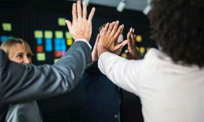 Team of IT workers give each other hi fives in support of each other