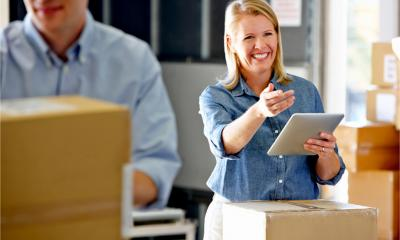 A smiling businesswoman prepares orders for shipping