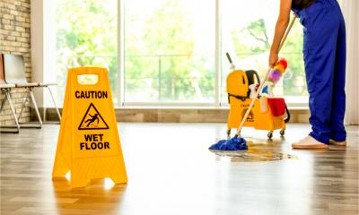 A professional cleaner mops the floor behind a safety sign