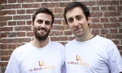 Two men stood in front of a wall with white t-shirts on saying La Belle Assiette