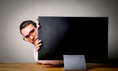 Man hiding behind monitor - avoid tax inspections