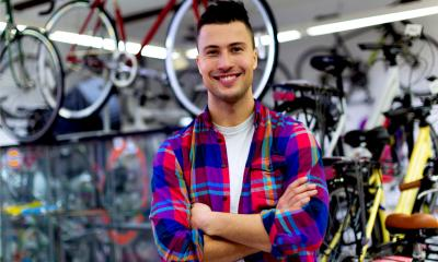 A male business owner poses in his bicycle shop