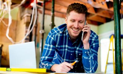A tradesperson smiles whilst taking a phone booking for another job