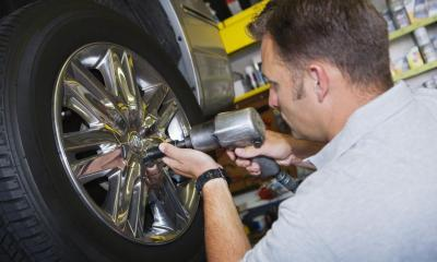 Tyre fitter attaching a wheel to a car in his garage