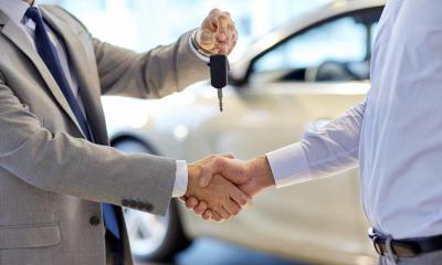 Car dealer handing the keys over to the new car buyer